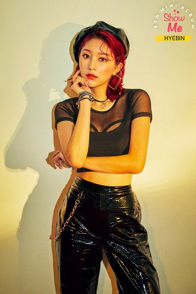 Tags: K-Pop, Momoland, Lee Hyebin, Pants, Brown Background, Bracelet, Chin In Hand, Necklace, Text: Album Name, Crossed Arms, Earrings, Closed Mouth