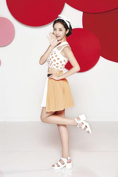 Tags: K-Pop, Girls' Day, Lee Hyeri, Hand On Hip, White Bow, Light Background, Pleated Skirt, Leg Up, Wave, Hair Bow, Spotted Background, White Background