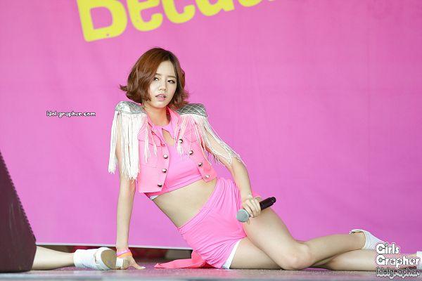 Tags: K-Pop, Girls' Day, Lee Hyeri, Shorts, White Footwear, Pink Shirt, Pink Jacket, Pink Background, Midriff, Sitting On Ground, Hand On Leg, Looking Away