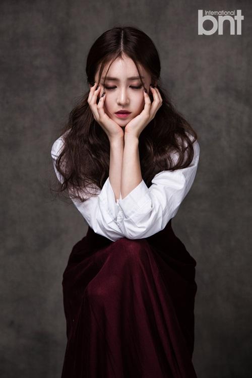 Tags: K-Drama, Lee Seul-bi, Red Skirt, Text: Magazine Name, Hand On Cheek, Hand On Head, Eyes Closed, Brown Background, Nail Polish, Skirt, Make Up, International Bnt