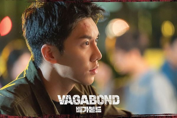 Tags: K-Drama, Lee Seung-gi, English Text, Logo, Serious, Side View, Injury, Brown Shirt, Text: Series Name, Looking Ahead, Korean Text, Vagabond