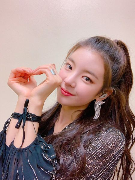 Tags: K-Pop, Itzy, Lia, Black Shirt, Hair Up, Ponytail, Brown Background, Heart Gesture