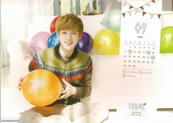 Tags: K-Pop, EXO, Luhan, Crossed Legs, Brown Outerwear, Balloons, Grin, Text: Calendar Date, White Pants, Couch, Sitting On Ground, Text: Artist Name