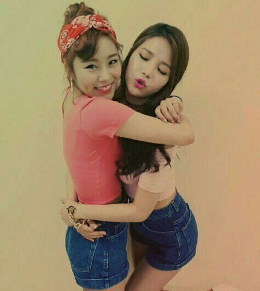 Tags: K-Pop, Mamamoo, Wheein, Solar, Eyes Closed, Arm Around Shoulder, Pink Shirt, Hug, Arm Around Waist, Shorts, Holding Close, Midriff