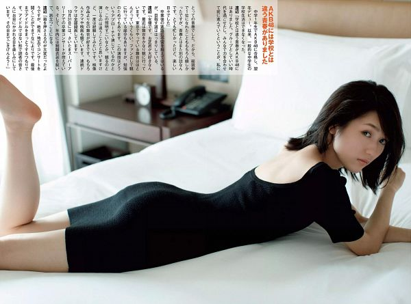 Tags: J-Pop, AKB48, Mayu Watanabe, Black Dress, Short Sleeves, Laying Down, Laying On Stomach, Japanese Text, Black Outfit, Barefoot, On Bed, Bed