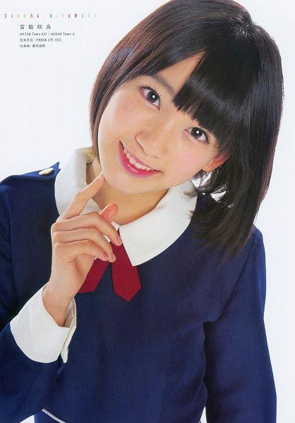 Tags: J-Pop, HKT48, Miyawaki Sakura, Light Background, Blue Outerwear, Red Bow, White Background, Red Neckwear, Medium Hair, Text: Artist Name, Bow, Chin In Hand