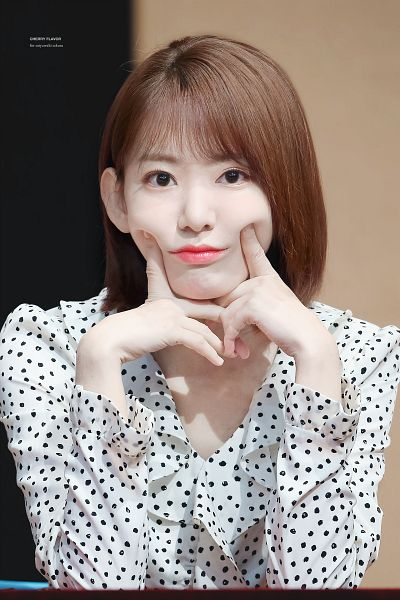 Tags: J-Pop, IZ*ONE, HKT48, Miyawaki Sakura, Finger To Cheek, Brown Background, Spotted, Spotted Shirt, Text: Artist Name, Medium Hair