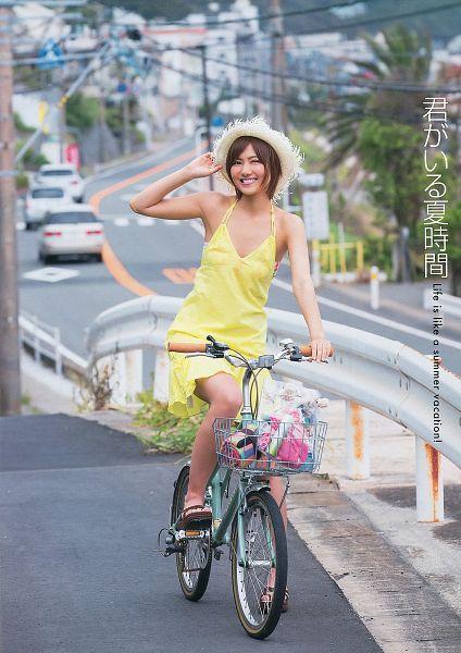 Tags: J-Pop, AKB48, Miyazawa Sae, Yellow Dress, White Headwear, Shoes, Japanese Text, English Text, Basket, Sandals, Outdoors, Wink
