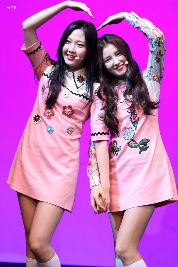 Tags: K-Pop, Momoland, Nancy, Kim Nayun, Two Girls, Heart Gesture, Looking Ahead, Duo, Pink Dress, Pink Background, Purple Background, Holding Hands