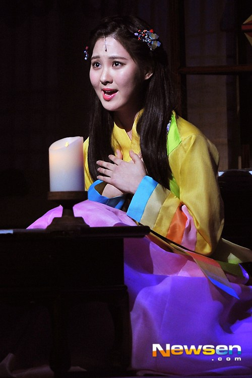 Tags: K-Pop, Girls' Generation, Seohyun, Yellow Shirt, Pink Skirt, Skirt, Hand On Chest, Black Background, Hair Ornament, Dark Background, Hanbok, Sitting On Ground