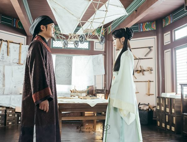 Tags: K-Drama, K-Pop, IU, Kim Sung-kyun, Traditional Clothes, Side View, Mustache, Skirt, Korean Clothes, Standing, Brown Outfit, Table