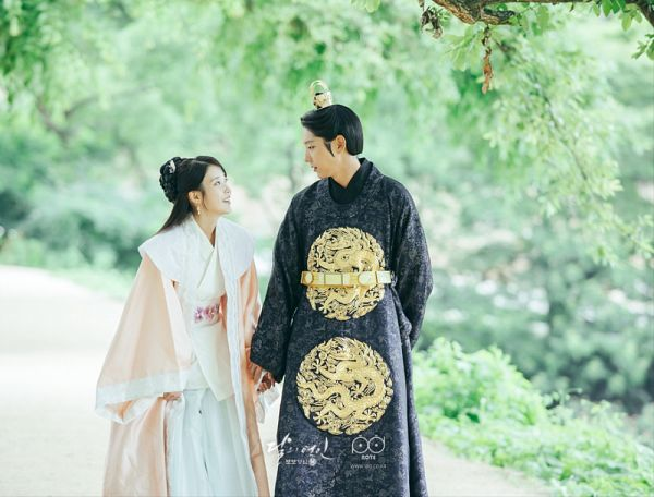 Tags: K-Drama, K-Pop, Lee Jun-ki, IU, Korean Clothes, Holding Hands, Plant, Looking At Another, Tree, Walking, Orange Shirt, Jewelry