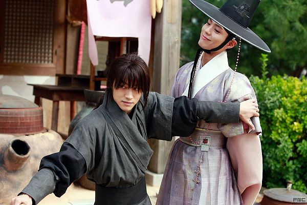 Tags: K-Drama, Park Bo-gum, Kwak Dong-yeon, Hair Up, Sword, Hand On Shoulder, Bush, Ponytail, Traditional Clothes, Standing, Plant, Korean Clothes