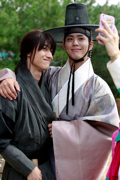 Tags: K-Drama, Park Bo-gum, Kwak Dong-yeon, Smartphone, Black Outfit, Two Males, Hair Up, Phone, Duo, Ponytail, Arm Around Shoulder, Traditional Clothes