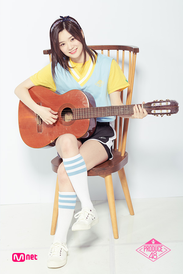 Tags: Television Show, J-Pop, AKB48, Nakano Ikumi, White Background, Black Shorts, Chair, Yellow Shirt, Sitting On Chair, Crossed Legs, Guitar, Short Sleeves