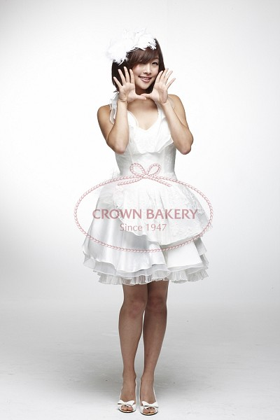 Tags: K-Pop, KARA, Nicole Jung, Bare Shoulders, Gray Background, Sleeveless, White Footwear, High Heels, Text: Brand Name, White Outfit, Bare Legs, White Dress