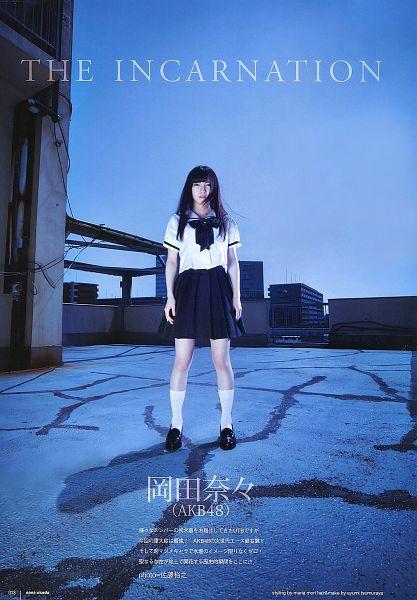 Tags: J-Pop, AKB48, Okada Nana, Blue Background, Bare Legs, Skirt, Collar (Clothes), Knee Socks, Black Skirt, Black Bow, Text: Artist Name, Shoes