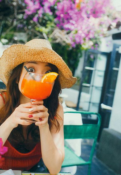 Tags: J-Pop, AKB48, Oshima Yuko, Hat, Brown Headwear, Red Shirt, Flower, Covering Mouth, Holding Object, Braids, Sitting On Chair, Outdoors