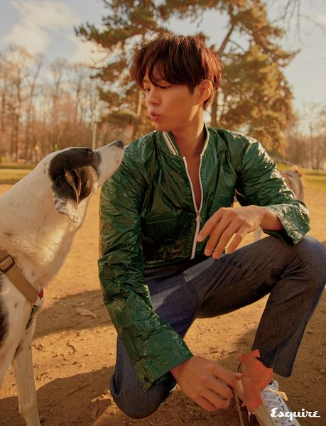 Tags: K-Drama, Park Bo-gum, Text: Magazine Name, Blunt Bangs, Pouting, Dog, Looking At Another, Animal, Shoes, Sneakers, Green Outerwear, Kneeling