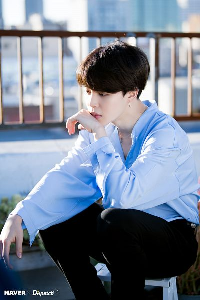 Tags: K-Pop, Bangtan Boys, Park Jimin, Black Eyes, Black Pants, Pants, Plant, Blue Shirt, Day, Sitting, Looking Ahead, City