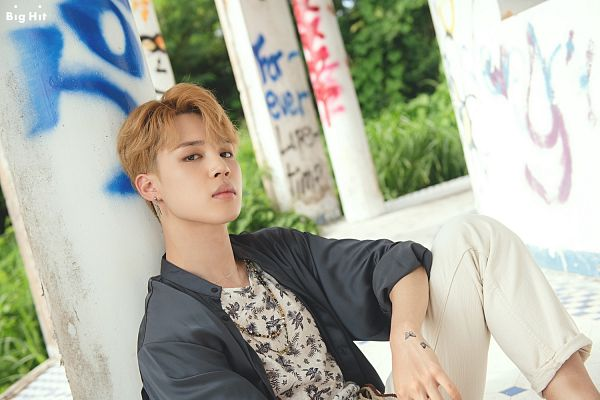 Tags: K-Pop, BTS, Park Jimin, Necklace, Text: Company Name, Grass, Sitting On Ground, Outdoors, Plant, English Text, Dutch Angle, Tattoo