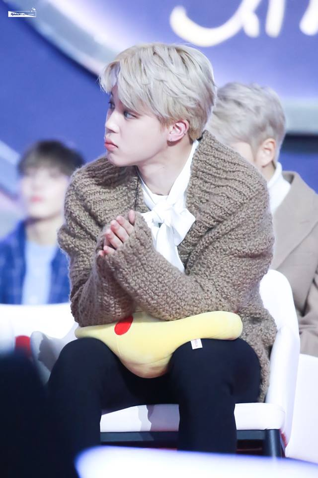 Tags: K-Pop, BTS, Park Jimin, White Neckwear, Brown Shirt, Sitting On Chair, Contact Lenses, Sweater, Looking Away, Toy, Chair, Bow