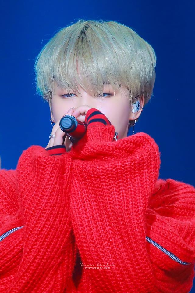 Tags: K-Pop, BTS, Park Jimin, Sweater, Earbuds, Pink Hair, Stage, Red Shirt, Contact Lenses, Singing, Blue Background