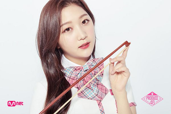 Tags: K-Pop, Television Show, Park Minji, Checkered Neckwear, Text: Series Name, Holding Object, Close Up, White Footwear, Bow Tie, Short Sleeves, Produce 48