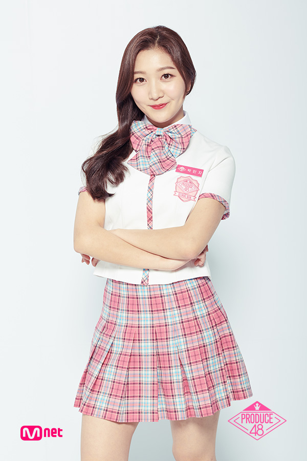 Tags: K-Pop, Television Show, Park Minji, Bow Tie, Text: Artist Name, Short Sleeves, Checkered Neckwear, Skirt, Checkered Skirt, Text: Series Name, White Footwear, Crossed Arms