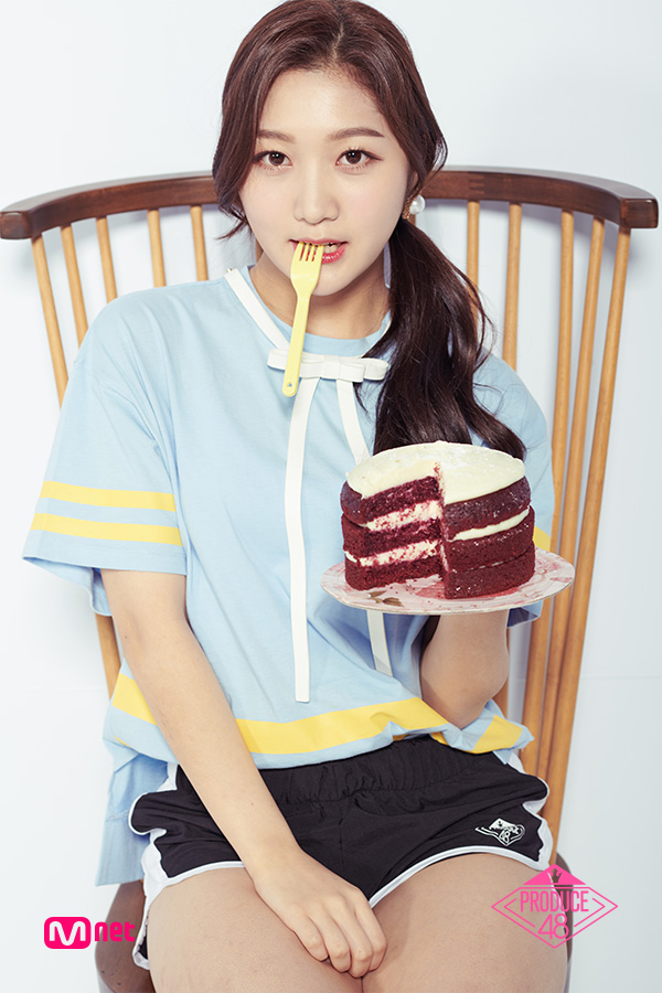 Tags: Television Show, K-Pop, Park Minji, Blue Shirt, Sitting On Chair, White Footwear, Shorts, Black Shorts, Holding Object, Text: Series Name, Bow Tie, Cake