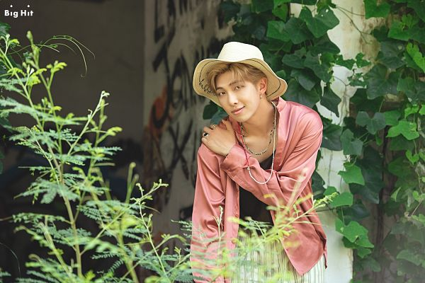 Tags: K-Pop, BTS, Rap Monster, Outdoors, Necklace, Plant, Leaf, Hat, Pink Jacket, Text: Company Name, Striped, English Text