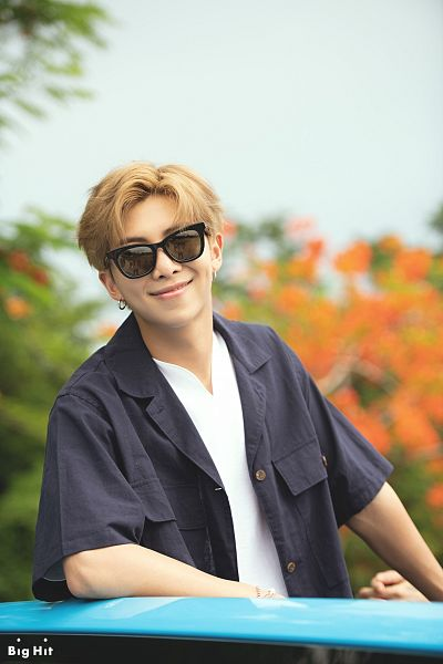 Tags: K-Pop, BTS, Rap Monster, Outdoors, Sunglasses, Text: Company Name, Sky, English Text, Open Shirt, Tree, Grin, Car