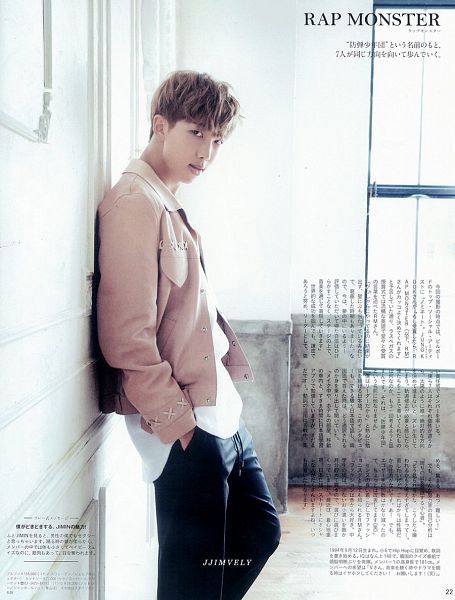 Tags: K-Pop, Bangtan Boys, Rap Monster, Black Pants, Japanese Text, Pants, Brown Outerwear, Hand In Pocket, Text: Artist Name, Leaning On Wall, Wall, Serious