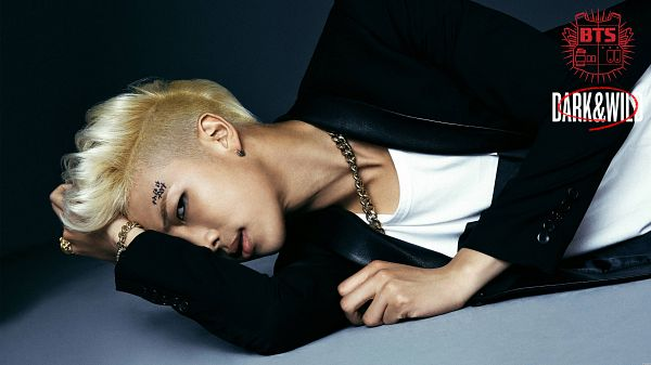Tags: K-Pop, BTS, Rap Monster, Black Jacket, Black Outerwear, Bracelet, Hand In Hair, Text: Album Name, Blonde Hair, Laying On Side, Blue Background, Laying Down