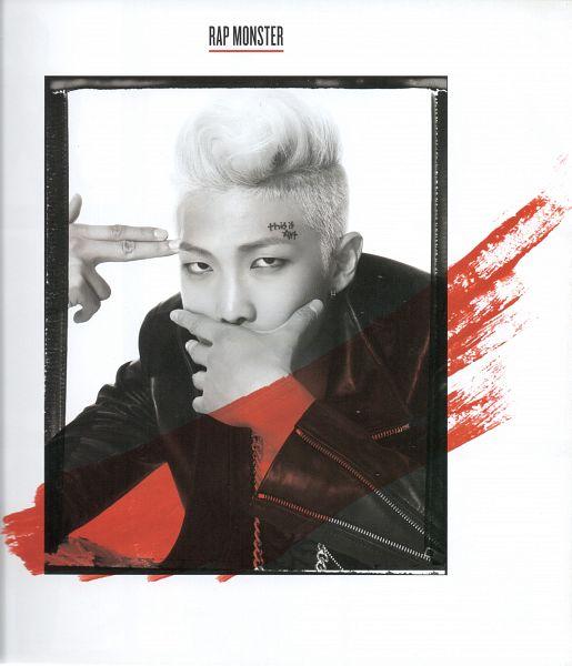 Tags: K-Pop, BTS, Rap Monster, White Background, Frame, Pointing, Text: Artist Name, Monochrome, Covering Mouth, Fingergun, Leather Jacket, Light Background
