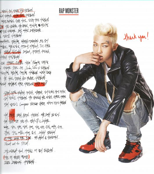 Tags: K-Pop, BTS, Rap Monster, Ring, Blue Pants, English Text, Black Outerwear, Necklace, Korean Text, Light Background, Crouching, Jeans