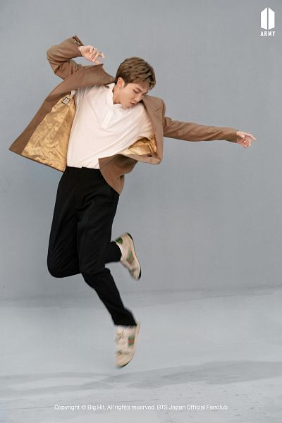 Tags: K-Pop, BTS, Rap Monster, Looking Down, Black Pants, Gray Background, Ring, Brown Outerwear, Black Eyes, Jumping, Shadow