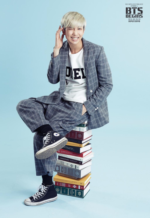 Tags: K-Pop, BTS, Rap Monster, Blue Background, Plaided Jacket, Gray Jacket, Plaided Pants, Book, Grin, Gray Outerwear, Wink, Gray Pants