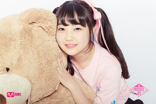 Tags: Television Show, J-Pop, AKB48, Sato Minami, Light Background, Pink Shirt, White Background, Stuffed Animal, Short Sleeves, Text: Series Name, Twin Tails, Bow