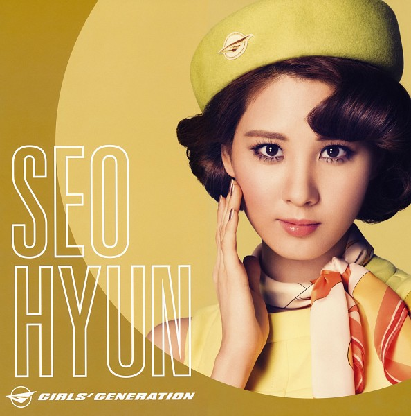 Tags: K-Pop, Girls' Generation, Seohyun, Yellow Background, Yellow Headwear, Scarf, Close Up, Text: Artist Name, Hat, Yellow Outfit, Hand On Cheek, Bare Shoulders