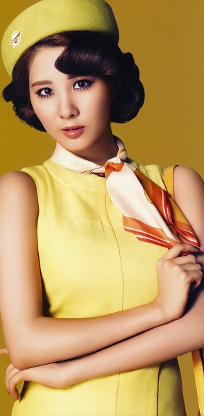 Tags: K-Pop, Girls' Generation, Seohyun, Scarf, Medium Hair, Yellow Headwear, Yellow Outfit, Sleeveless, Brown Background, Yellow Dress, Bare Shoulders, Hat