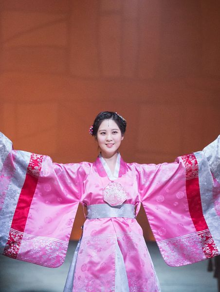 Tags: K-Pop, Girls' Generation, Seohyun, Hair Up, Pink Outfit, Looking Away, Hair Ornament, Traditional Clothes, Brown Background, Hanbok, Pink Dress, Arms Out