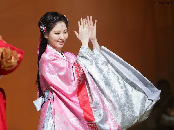 Tags: K-Drama, Girls' Generation, Seohyun, Eyes Half Closed, Hair Up, Brown Background, Looking Down, Ponytail, Pink Outfit, Pink Dress, Clapping, Hanbok