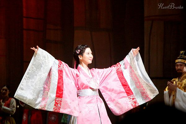 Tags: K-Drama, Girls' Generation, Seohyun, Hanbok, Arms Out, Hair Up, Hair Ornament, Pink Outfit, Looking Away, Brown Background, Looking Up, Traditional Clothes