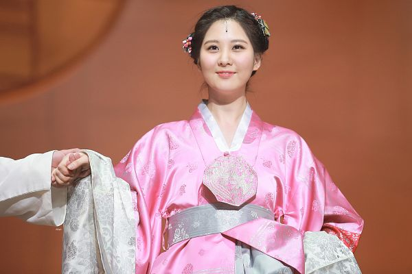 Tags: K-Drama, Girls' Generation, Seohyun, Traditional Clothes, Pink Dress, Holding Skirt, Hanbok, Hair Ornament, Skirt, From Below, Holding Hands, Brown Background