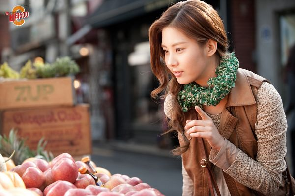 Tags: SM Town, K-Pop, Girls' Generation, Seohyun, Fruits, Korean Text, Pointing, Outdoors, Looking Down, Apple, Scarf, Brown Outerwear