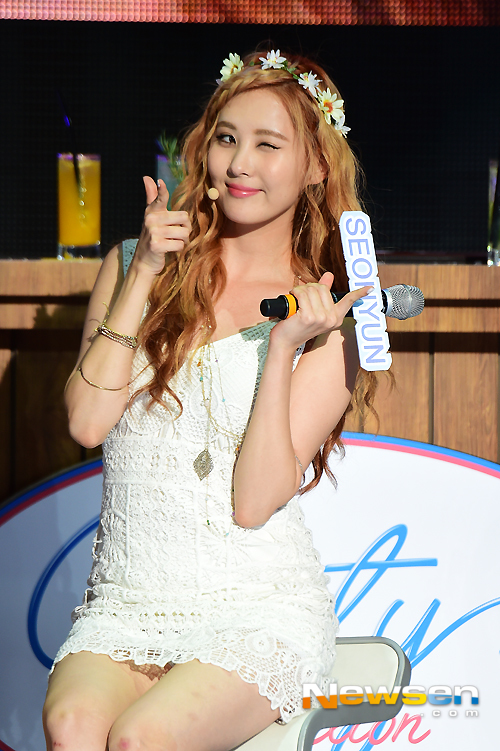 Tags: K-Pop, Girls' Generation, Seohyun, Chair, Text: Artist Name, White Dress, Flower, Sitting On Chair, White Outfit, Pointing, Hair Flower, Wink