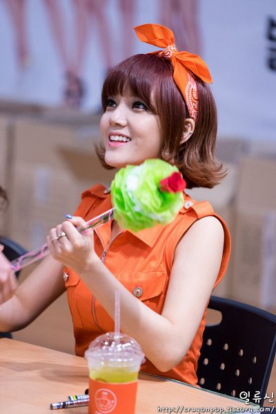 Tags: K-Pop, AOA (Ace Of Angels), Shin Jimin, Looking Up, Flower, Sitting On Chair, Bandana, Sleeveless, Orange Headwear, Orange Shirt, Chair, Bare Shoulders