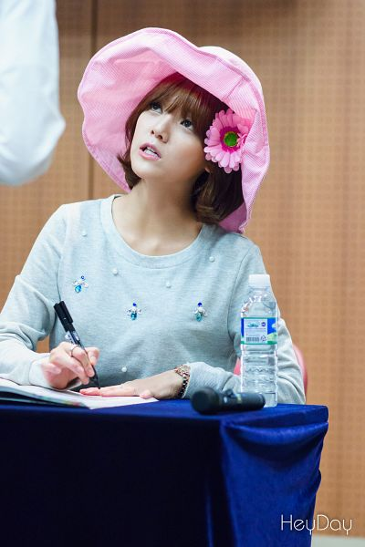 Tags: K-Pop, AOA (Ace Of Angels), Shin Jimin, Blue Shirt, Pink Headwear, Hat, Brown Background, Bracelet, Sweater, Sitting On Chair, Water, Chair