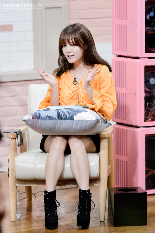 Tags: K-Pop, AOA (Ace Of Angels), Shin Jimin, Skirt, Black Skirt, Chair, Black Footwear, Pillow, Boots, Orange Shirt, Sitting On Chair, Phone